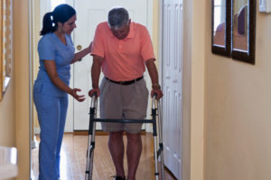 Home haaealthcare - Hispanic nurse at home of senior man (60s) using walker.